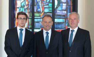 drei Männer vor einem Kirchenfenster, Foto: Bestattung Wolfsberg